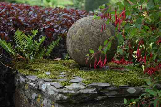 Sometimes shabby chic works in the garden as well as in the home. A moist, mild climate creates the sort of combination of moss and fern that makes stone,  berberis and fuchsia not just nice but beautiful
